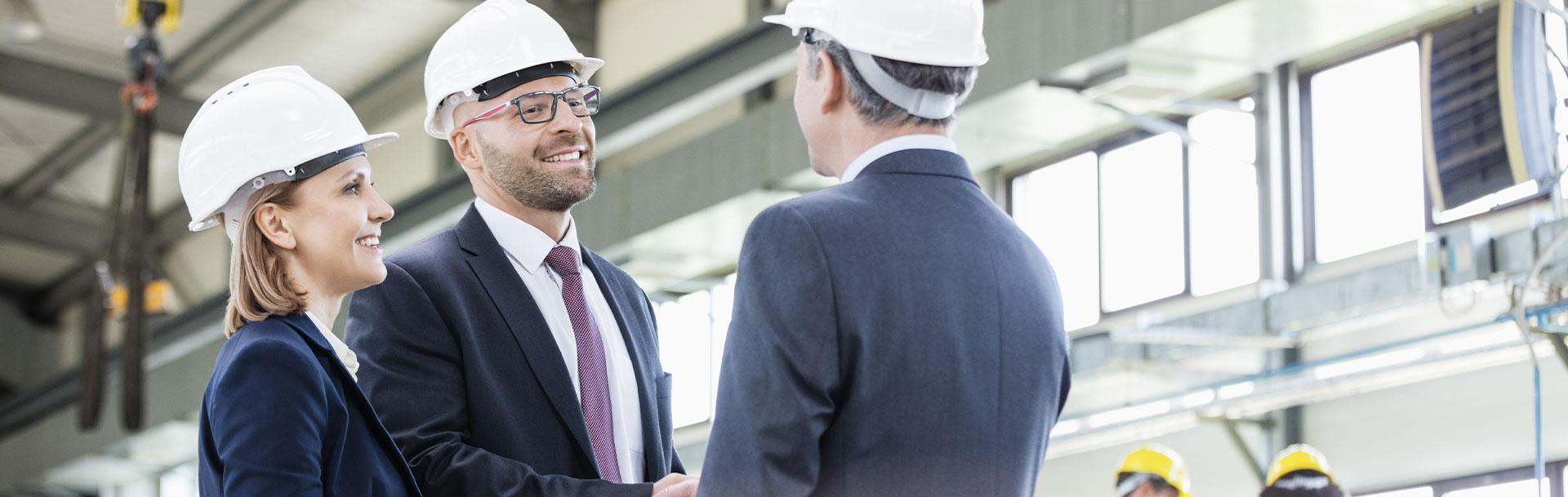 Drei Personen mit weißen Helmen in Business-Anzügen